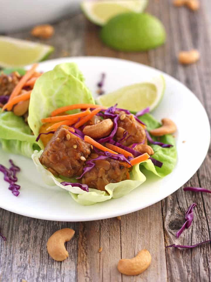 Sriracha Tempeh Lettuce Wraps. Butter lettuce cups filled with baked tempeh, onions and peppers topped with crispy cabbage, carrots and cashews. A satisfying vegetarian dinner for two.