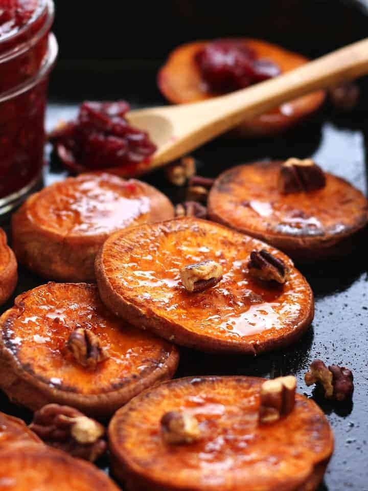Roasted Sweet Potato Rounds are seasoned with coconut oil, salt and cinnamon then roasted to caramelized perfection. Drizzle with maple syrup, roasted cranberries and toasted pecans for an irresistible Thanksgiving snack or side dish for two.