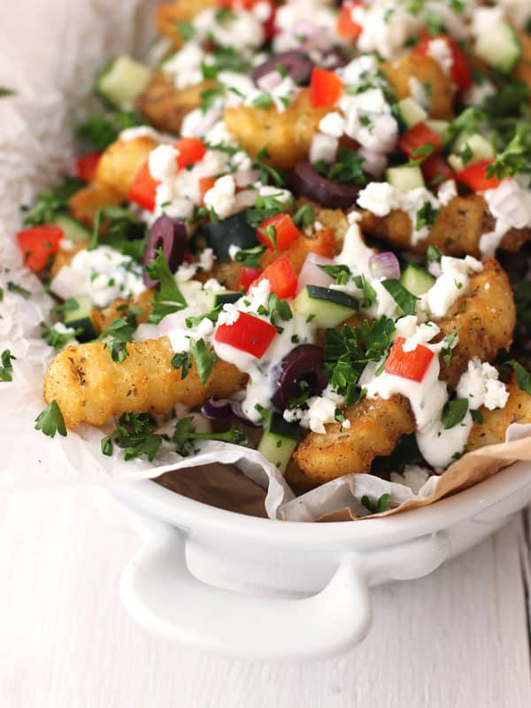 Toaster oven Greek fries are the perfect midnight snack. Crispy toaster oven baked frozen fries covered with a yogurt sauce, fresh veggies and feta cheese.