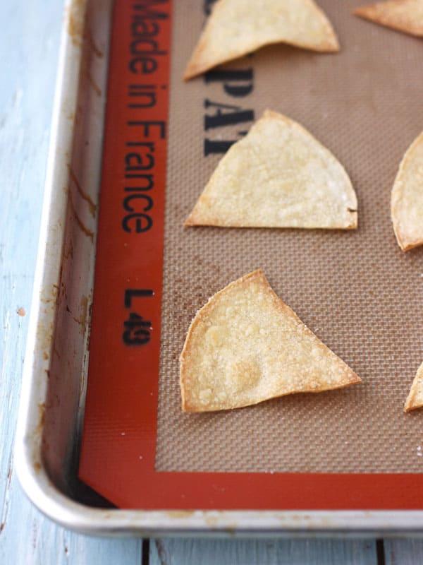 White corn tortilla chips cooling on baking pan.