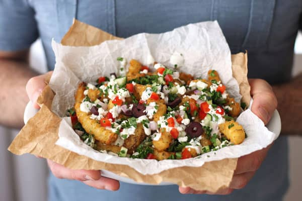 Toaster oven Greek fries covered with a tangy yogurt sauce, fresh veggies and feta cheese. Better make extra, these will go fast.