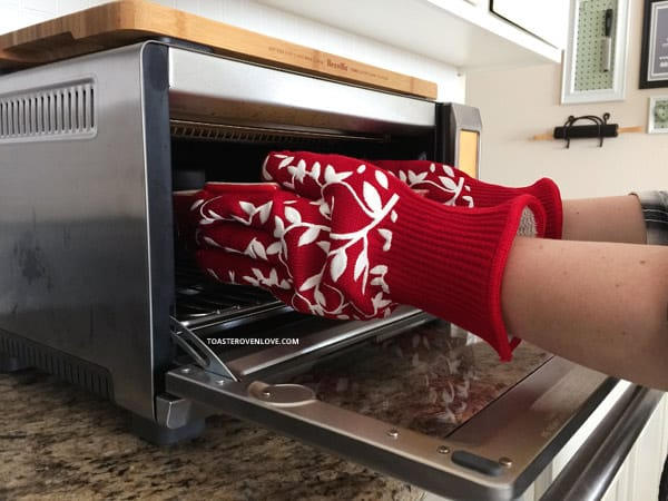 hands covered with red oven gloves reaching into a toaster oven
