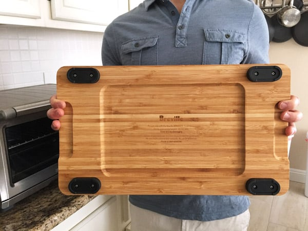 Person holding cutting board showing underside and feet