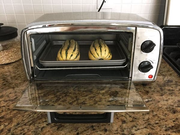 two halves of delicata squash in a small toaster ovens