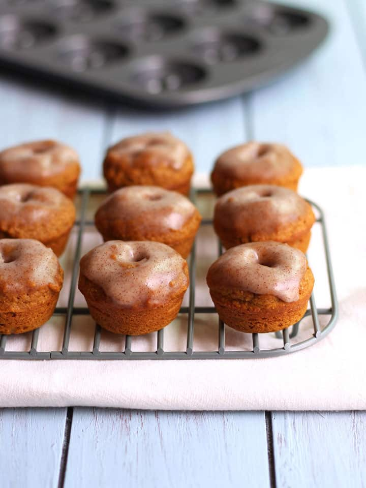 Cinnamon Glazed Whole Wheat Mini Pumpkin Donuts. Perfectly spiced and generously glazed healthier baked pumpkin mini donuts.
