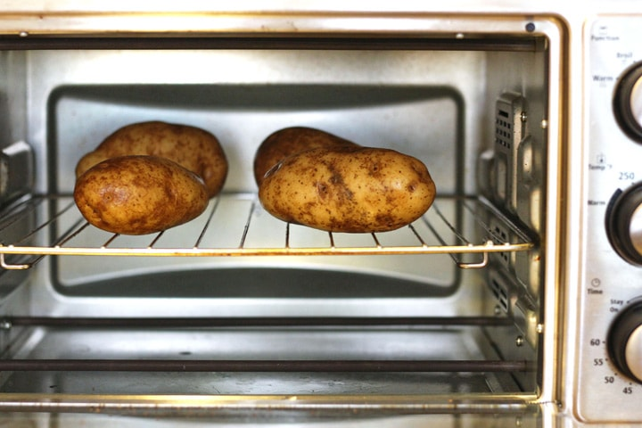 Toaster Oven Baked Potatoes, a simple step by step picture guide for making crispy skinned fluffy baked potatoes in your toaster oven. Enjoy one tonight!