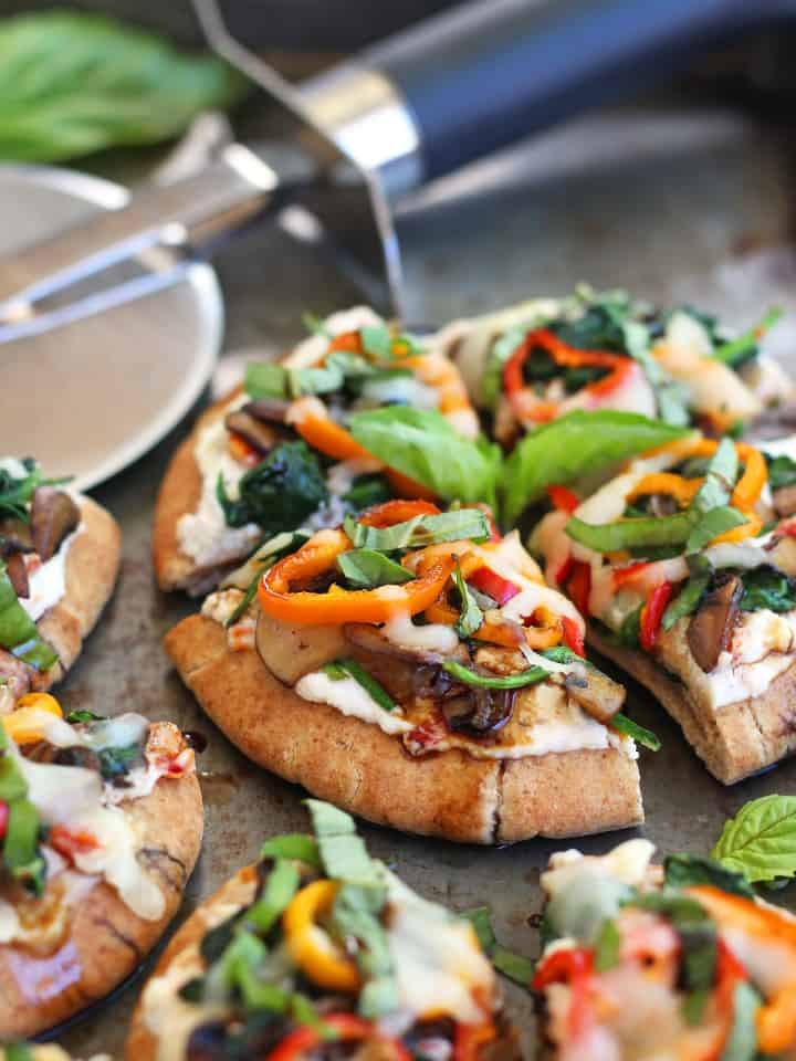 "Veggie Pita Pizza Bites. Add a little green to your next Super Bowl party with some mini veggie topped pizza bites. Whole wheat mini pitas, ricotta, sun dried tomatoes, sautéed mushrooms, spinach and bell pepper slices. Serve drizzled with balsamic vinegar and watch these ""pizza bites"" disappear."