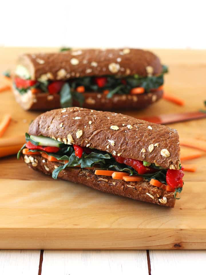 Roasted Red Pepper, Carrot and Hummus Sandwich. A toasted whole wheat baguette layered with hummus, avocado, roasted red peppers, matchstick carrots and generously topped with fresh veggies. Vegan or vegetarian with cheese.