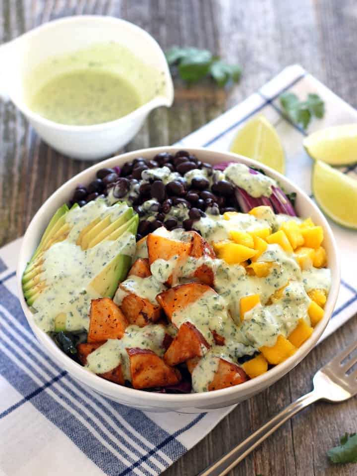 Mango Sriracha Potato Veggie Bowls. Crunchy red cabbage and kale topped with spicy sriracha roasted red potatoes, sweet mango, avocado and black beans. Drizzled liberally with a tangy cilantro lime dressing. A sweet, spicy, tangy vegetarian lunch for two.