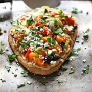 Veggie Hummus Flatbread. Olive oil and Za'atar seasoned flatbread smothered in hummus and topped with artichokes, Kalamata olives, tomatoes, cucumbers, bell peppers, parsley and feta cheese. A quick and healthy meat-free lunch for two.