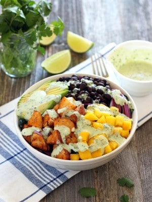 A white bowl filled with potatoes, mango, avocado and black beans next to a saucer of dressing, lime wedges and a mason jar filled with fresh cilantro.