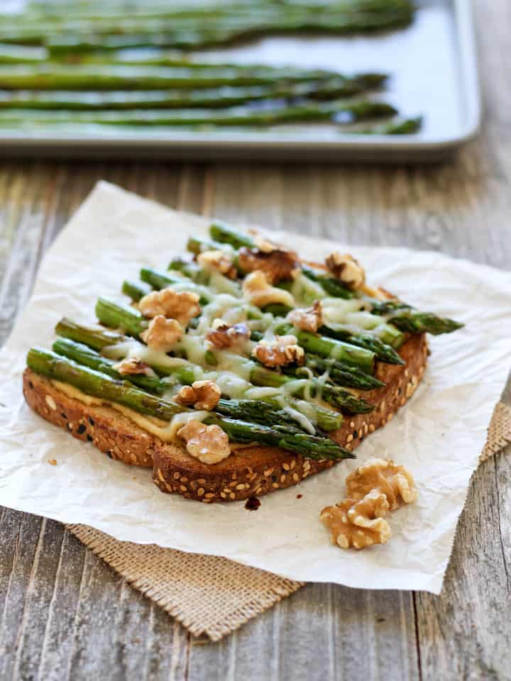 Balsamic Asparagus and Hummus Toast. A light but filling vegetarian lunch of whole grain toast topped with hummus, roasted asparagus, melted cheese, walnuts and a drizzle of balsamic vinegar.