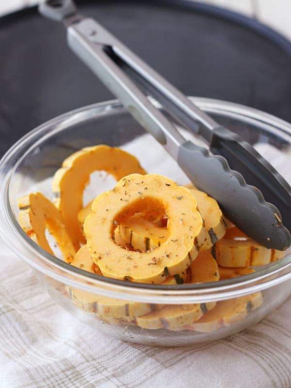 Seasoned slices of delicata squash in a bowl
