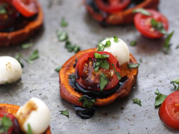 Baked sweet potato slices topped with mini mozzarella balls, tomatoes, fresh basil and a drizzle of tangy balsamic glaze are the perfect appetizer for your next party