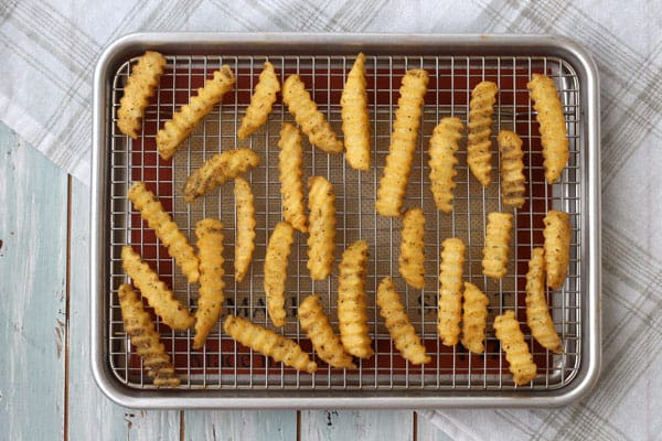 Frozen fries taste amazing seasoned before cooking. Add a little oil, your favorite seasoning and use a baking rack to cook in your toaster oven.