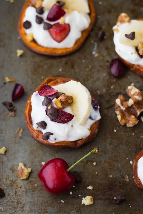 Cherry Banana Split Sweet Potato Rounds are the most fun you'll have at breakfast this week. Top baked sweet potato slices with yogurt, cherries, banana slices and mini chocolate chips for a fun treat.