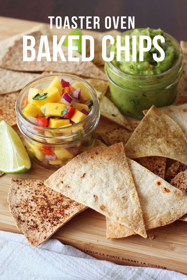 Baked tortilla chips with salsa and guacamole on a cutting board.