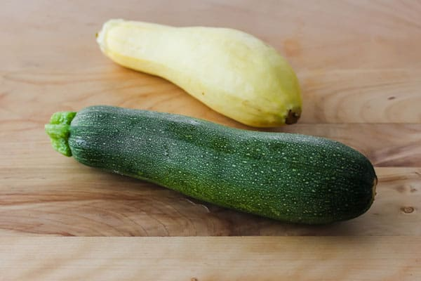 Fresh zucchini and yellow summer squash on a cutting board.