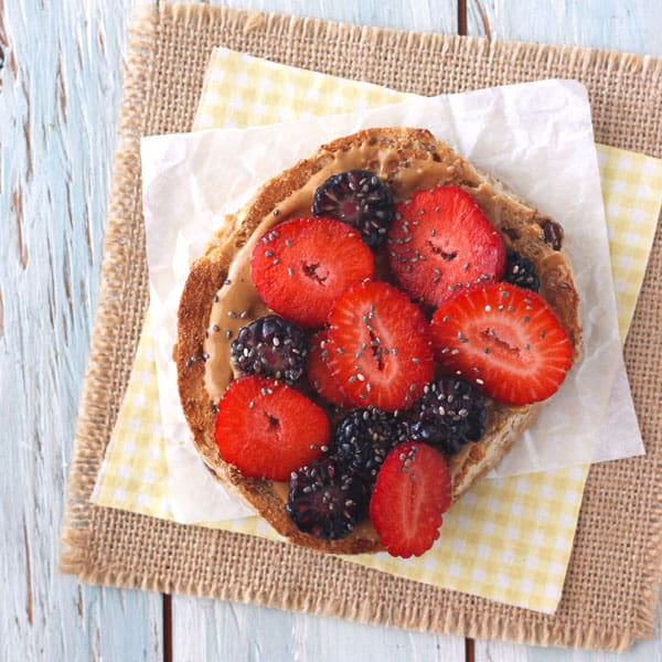 A whole grain bagel topped with peanut butter, fresh berries and chia seeds.