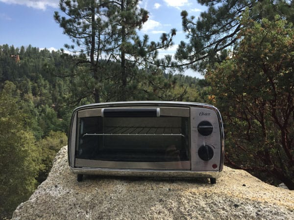 Toaster oven on a boulder in the forest.
