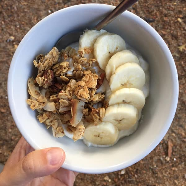 A white bowl with Greek yogurt, clumpy granola and sliced bananas.