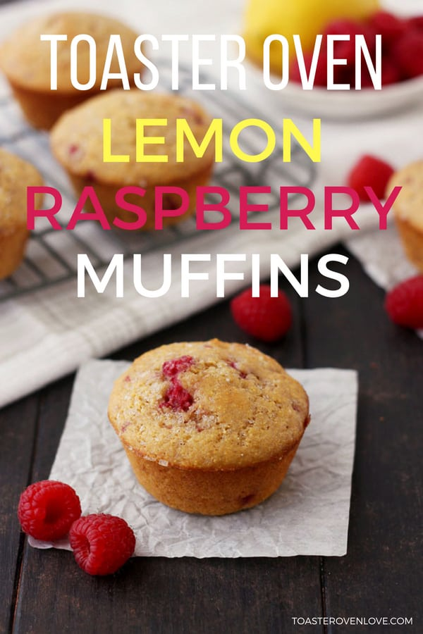 A baked raspberry lemon corn muffin on a table with fresh raspberries.