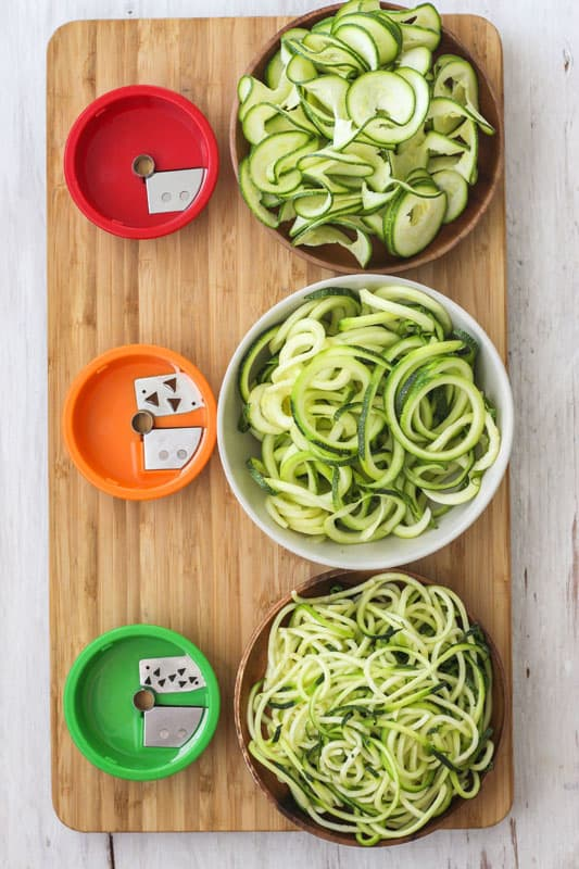 3 types of zucchini noodles in bowls next to their corresponding blade attachment.
