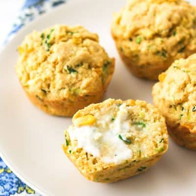 Cornbread zucchini muffins on a plate sliced in half and spread with butter.