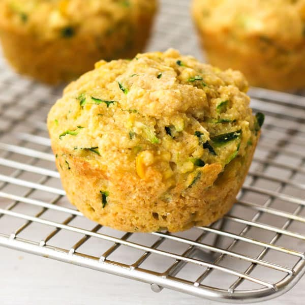 Cornbread zucchini muffins cooling on a silver metal baking rack.