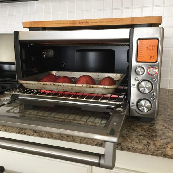 A quarter sheet pan of sweet potatoes inside a Breville Smart Oven Pro.