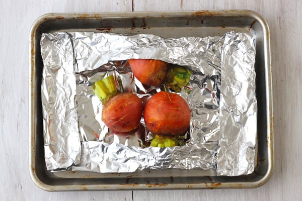 Beets wrapped in foil on a quarter sheet pan