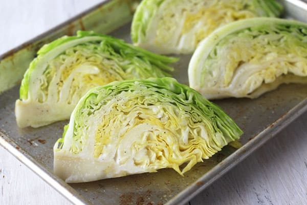 Oiled and seasoned cabbage wedges on a quarter sheet pan.
