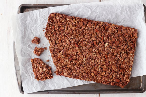 Large piece of baked granola on a piece of parchment paper.