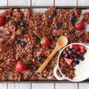 Small batch chocolate granola on a baking sheet with fresh berries.