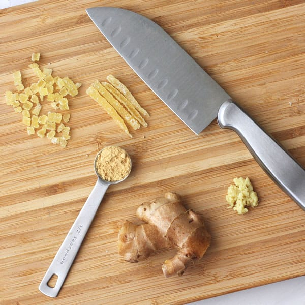 3 types of ginger (fresh, powdered and candies) on a cutting board with a knife.