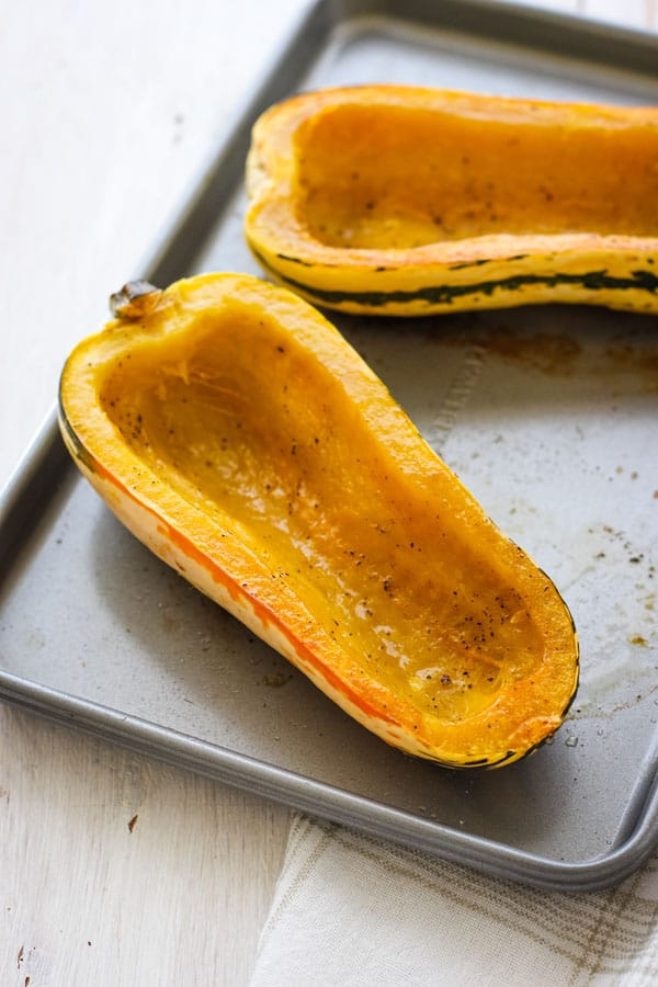 Empty roasted delicata squash boats on a toaster oven baking sheet.