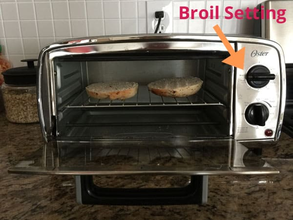 Small toaster oven with bagel slices inside and an arrow pointing to the Broil setting.
