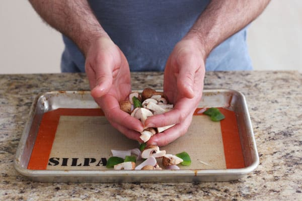Hands tossing vegetables with oil on a baking sheet.