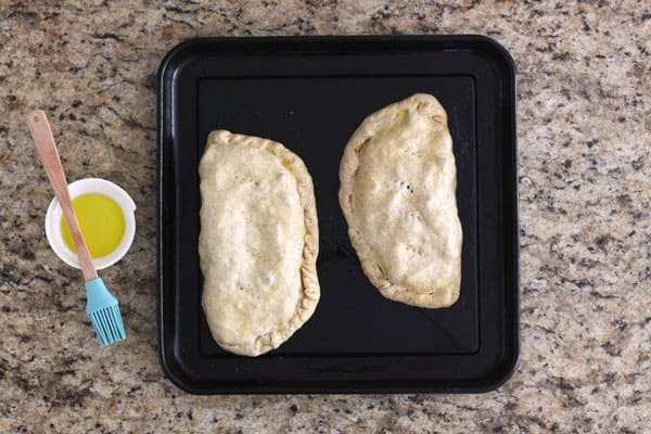 Filled calzones on a toaster oven baking pan.