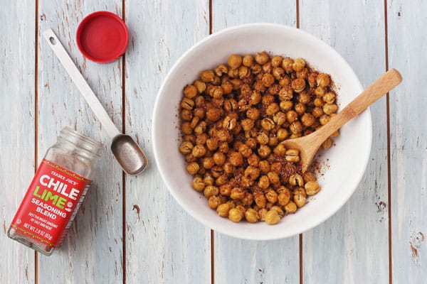 Dry roasted chickpeas in a white bowl next to a jar of chile lime seasoning.