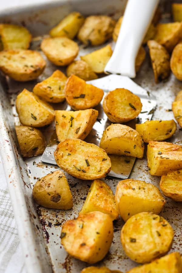 Roasted potatoes on a metal baking pan with a spatula.