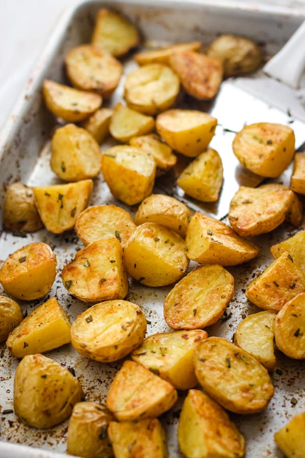 Toaster Oven Rosemary Potatoes on a quarter sheet pan with a metal spatula.