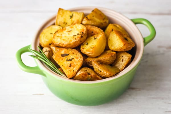 Roasted rosemary potatoes in a small green oval baking dish on a white background.