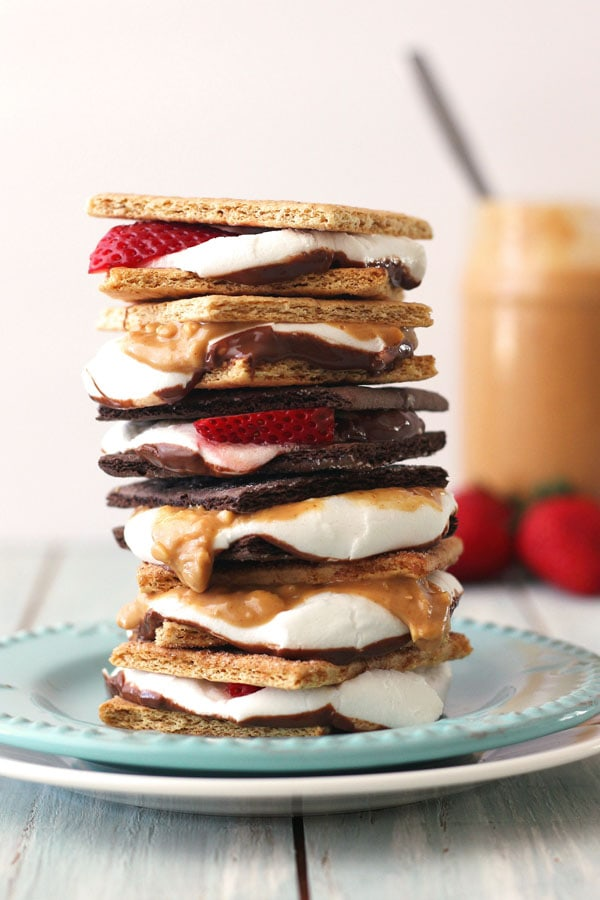 A tall stack of cinnamon, chocolate and original graham cracker s'mores with strawberries and peanut butter.