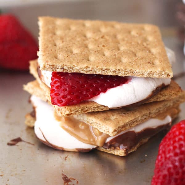 Toaster oven s'mores with fresh strawberry slices and peanut butter on a pan.