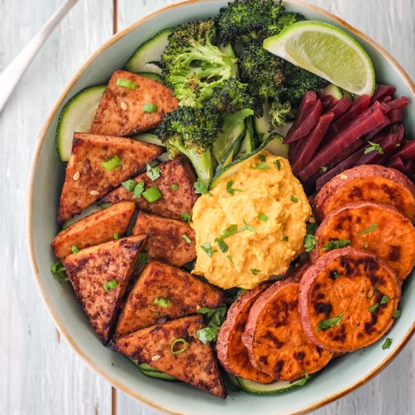 Broiled tofu in a bowl with zucchini spirals, sweet potato round, broccoli and hummus.