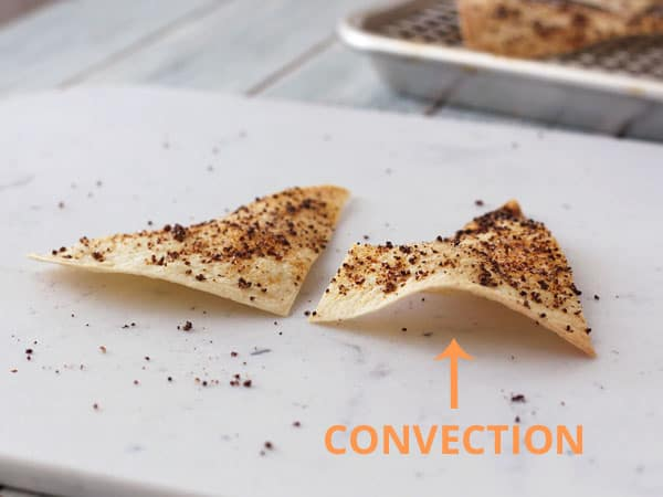 Chips side by side on a cutting board with arrow pointing to convection baked chip.