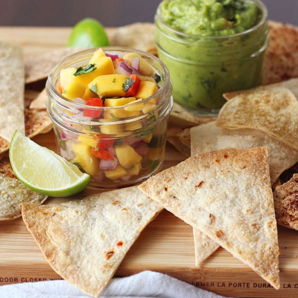 Baked tortilla chips on a platter with salsa and guacamole.